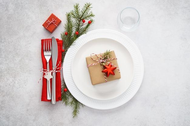 Kersttafel met witte borden, rood servet en bestek