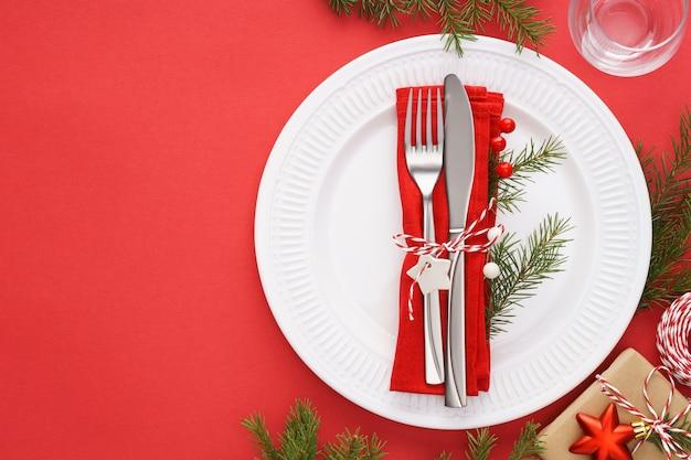 Kersttafel met witte borden, servet en bestek