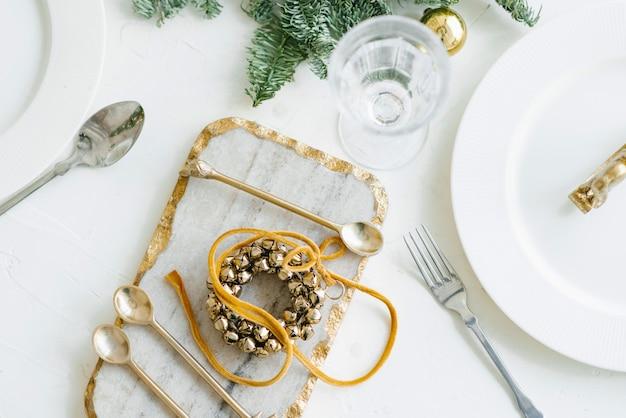 Kersttafel setting, klassiek decor met een krans van golden bell