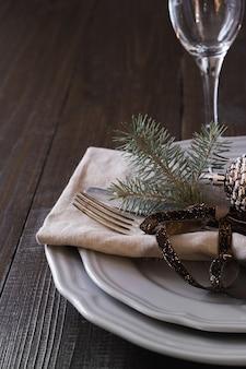 Kersttafelsetting met zilverwerk en donker natuurlijk groenblijvend decor.