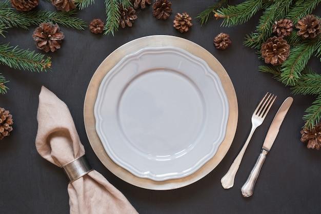 Kersttafelsetting met zilverwerk en een donker groenblijvende inrichting.
