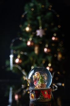 Kersttafereel met boom, lichten en sneeuwbol. selectieve aandacht