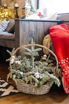 Kersttakken van sparren of sparren in een compositie met katoen in een rieten mand als decor in huis