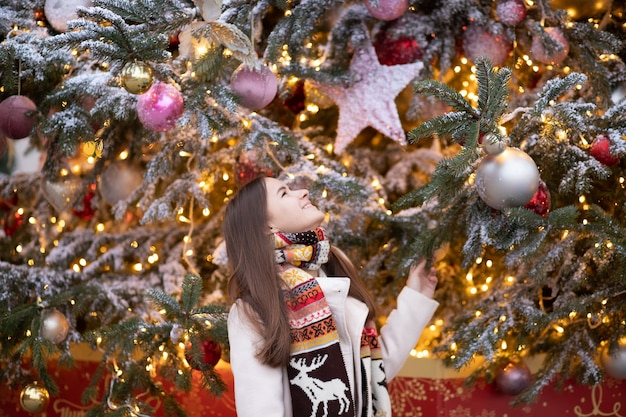 Kerstthema jong mooi europees meisje op een achtergrond van een kerstboom