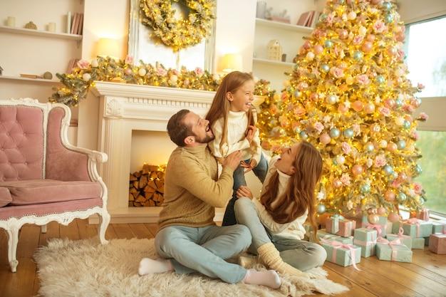 Kersttijd. jong gezin voelt zich gelukkig zittend in de buurt van de nieuwe jaarboom
