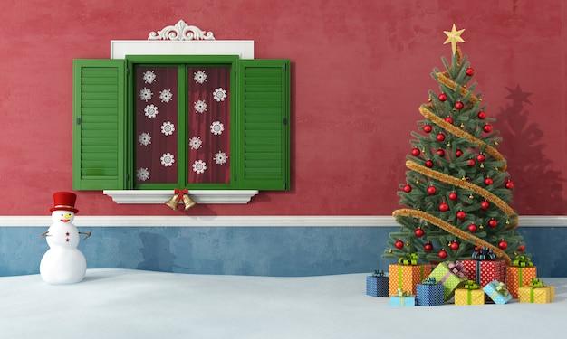 Kersttijd, kerstboom in sneeuw, naast venster