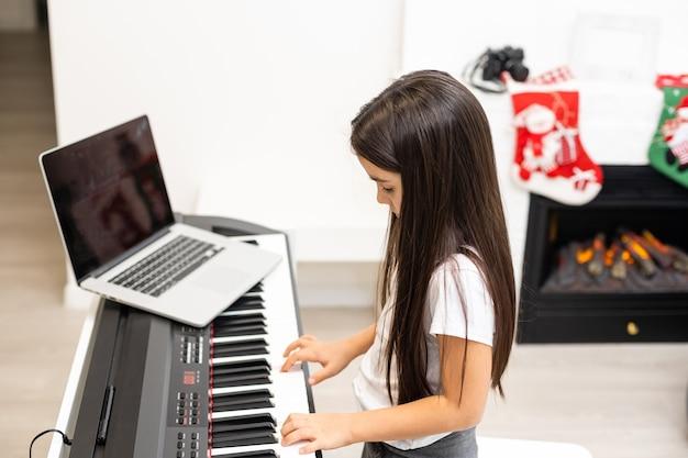 Kersttijd, laptop op pianotoetsen, klein meisje dat piano speelt