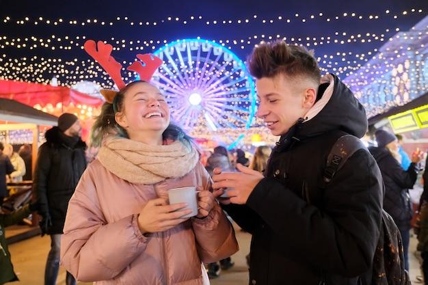 Kersttijd, nieuwjaarsvakantie. jongeren, een paar tieners die plezier hebben op de kerstmarkt