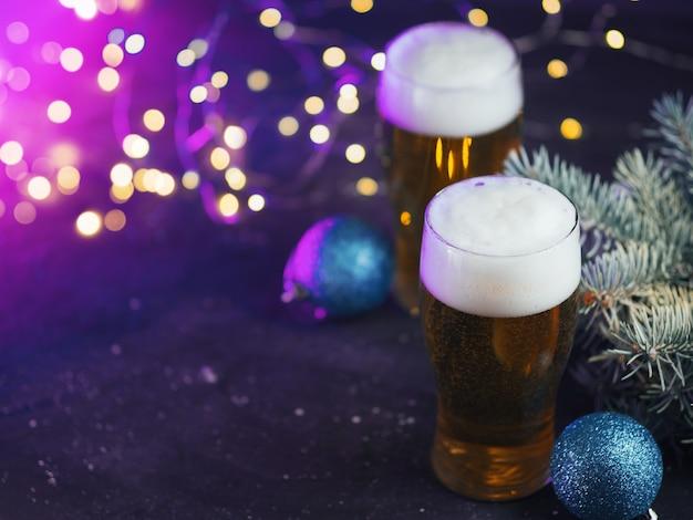 Kersttoostkaart, twee glazen light bier op een gekleurde neonachtergrond met slingers en kopieerruimte