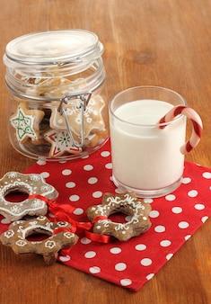 Kersttraktaties en glas melk op houten tafel close-up