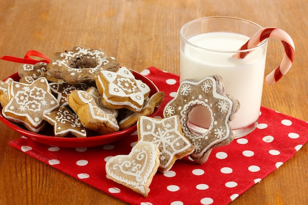 Kersttraktaties op bord en glas melk op houten tafel close-up