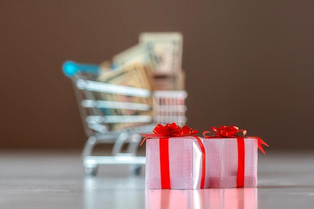 Kerstuitgaven planning concept, geschenkdozen met winkelwagentje vol geld op onscherpe achtergrond