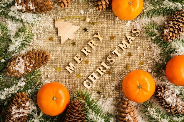 Kerstvakantie achtergrond met de letters van merry christmas, citrus, sparren takken en kegels. bovenaanzicht. jute.