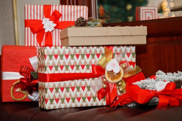 Kerstvakantie achtergrond van dozen met gelukkig nieuwjaar geschenken onder versierde kerstboom op stoel. geschenken schoonheid verpakt met linten. decor onder boom in interieur. detailopname. ruimte kopiëren