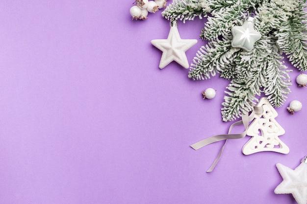 Kerstvakantie compositie met witte kerstversiering en sparren takken op paars