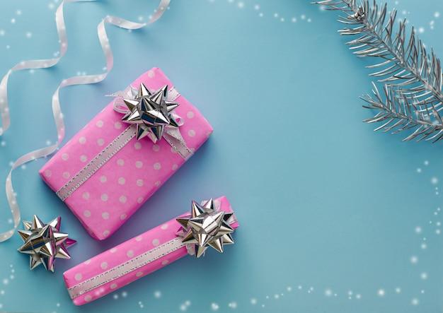 Kerstvakantie decoraties. roze geschenkdozen op pastel blauwe achtergrond. frame samenstelling, kopie ruimte