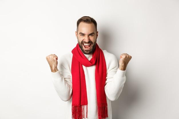 Kerstvakantie en nieuwjaar concept. gelukkige man die de overwinning viert, wint en vuistpompen maakt, doel bereikt, ja zegt terwijl hij op een witte achtergrond staat