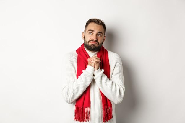 Kerstvakantie en nieuwjaar concept. trieste en ellendige man die tot god bidt, met en hand in hand bidt, omhoog kijkt naar de lucht en smeekt, staande op een witte achtergrond.