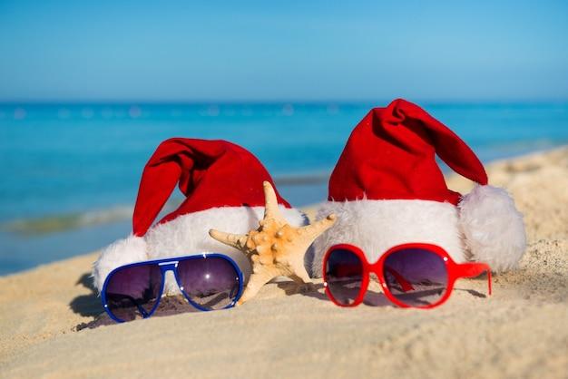 Kerstvakantie en romantisch nieuwjaar op zee. kerstmutsen en zonnebrillen op zandstrand