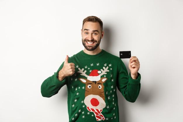 Kerstvakantie en winkelconcept gelukkige bebaarde man met creditcard en duim omhoog aanbevelen...