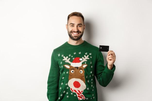 Kerstvakantie en winkelconcept jonge man in wintertrui met creditcard die over...