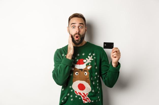 Kerstvakantie en winkelconcept man die creditcard toont en er verbaasd uitziet terwijl hij over...