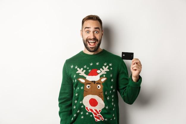 Kerstvakantie en winkelconcept vrolijke man die een creditcard toont die op een witte achtergrond staat