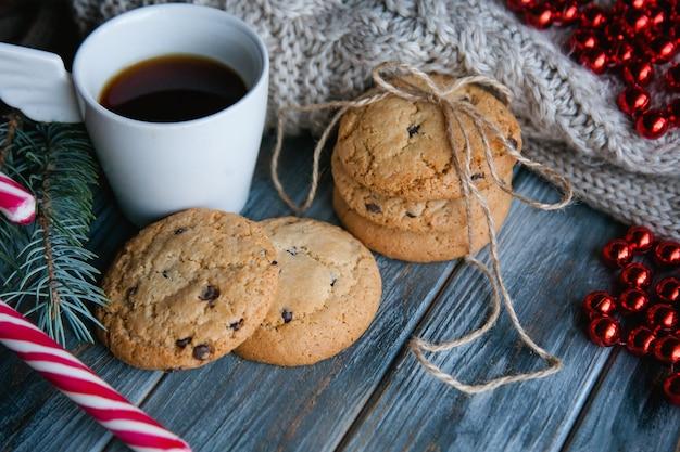 Kerstvakantie eten snack concept. chocoladeschilferkoekjes en een mok thee op houten ondergrond. seizoensgebonden decoratie.