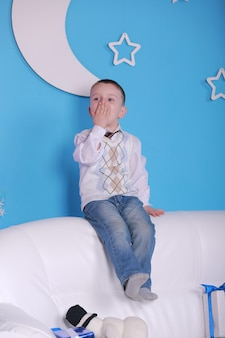 Kerstvakantie. kleine jongen op een witte sofa met kerstcadeautjes doos. blauwe muur met een witte maan op een muur.