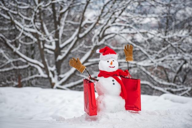 Kerstvakantie kortingen en winteruitverkoop. sneeuwpop in een sjaal en muts met boodschappentas. gelukkig