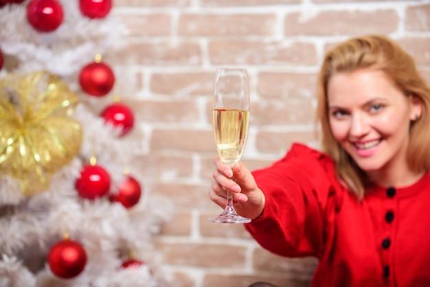 Kerstvakantie. meisje vieren in de buurt van kerstboom. vrouw houdt glas champagne. dame viert kerst. vrolijk kerstfeest. proost concept. meisje met champagneglas ontspannen in de buurt van kerstboom.