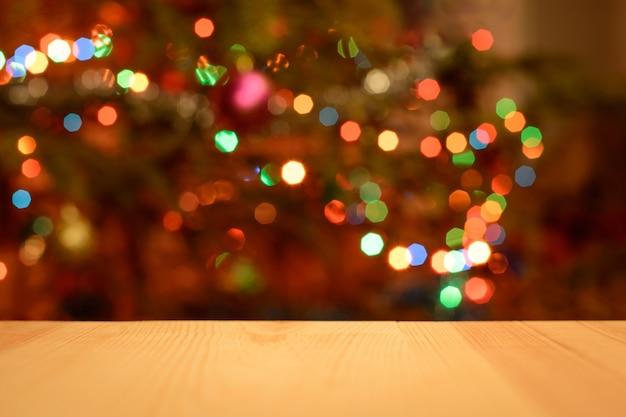 Kerstvakantie met lege houten bureautafel over versierde kerstboom