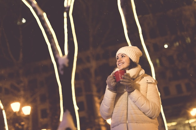 Kerstvakantie mooie lachende vrouw in warme kleding met kop warme koffie buiten in de winter