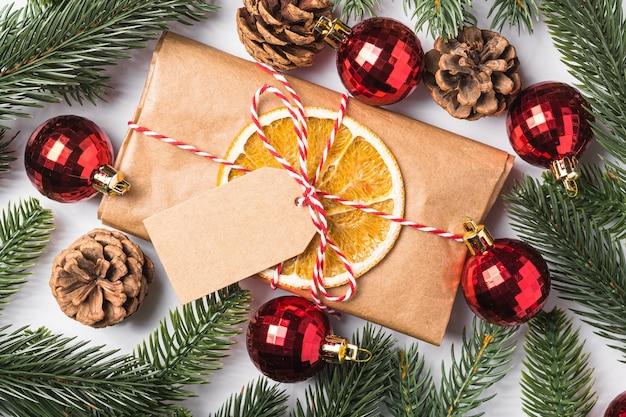Kerstvakantie nul afvalpapier geschenkverpakking met tag, kerstballen, gedroogd fruit en dennentakken