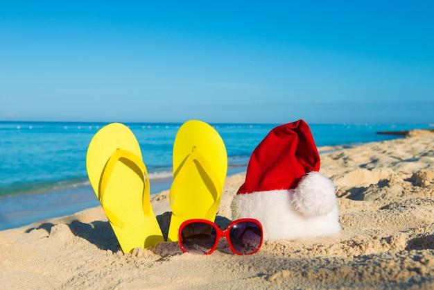 Kerstvakantie op zee. gelukkig nieuwjaar vakantie. kerstmuts, sandalen, zonnebril op zandstrand