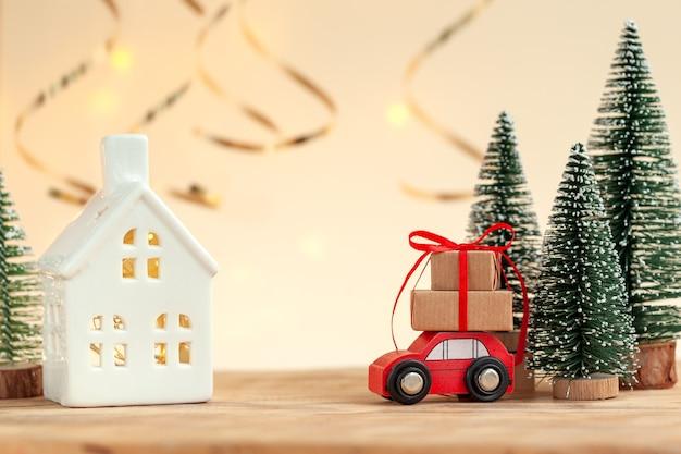 Kerstvakantie samenstelling met decoratieve keramische huis en rode speelgoedauto met stapel kerst geschenkdozen.