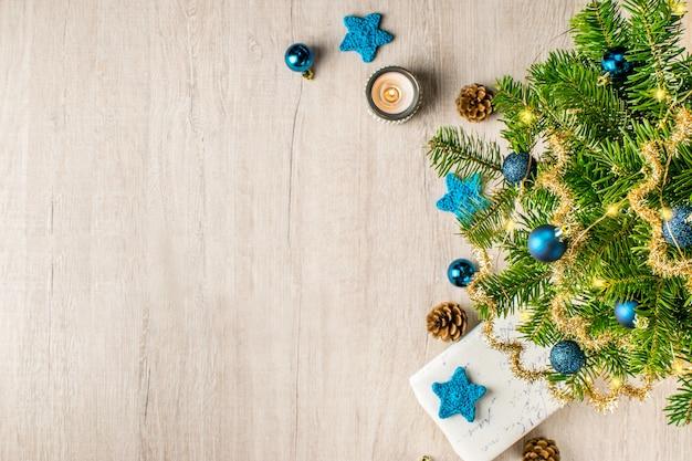 Kerstvakantie samenstelling voor uw wintervakantie berichten. kerstcadeau en lichten, dennenappels, sneeuwvlokken, kaars, blauwe sterren, klatergoud en kerstballen op een getextureerde hout.