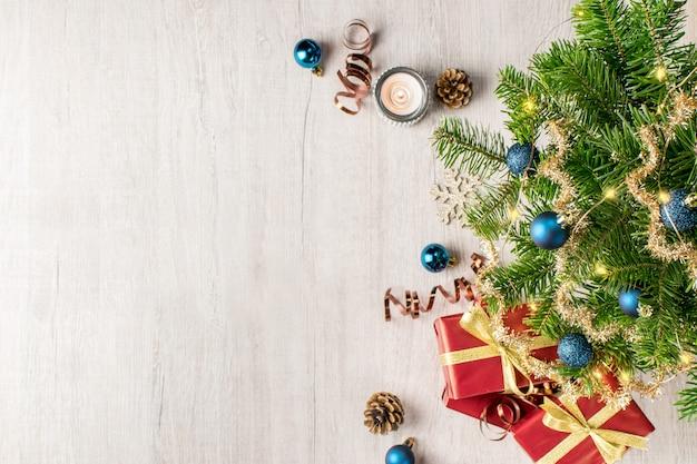 Kerstvakantie samenstelling voor uw wintervakantie berichten. kerstcadeau en lichten, dennenappels, sneeuwvlokken, kaars, klatergoud en kerstballen op een getextureerde hout.