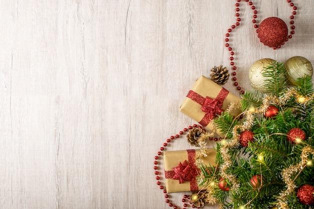 Kerstvakantie samenstelling voor uw wintervakantie berichten. kerstcadeau en lichten, dennenappels, sneeuwvlokken, klatergoud en kerstballen op een getextureerde hout.