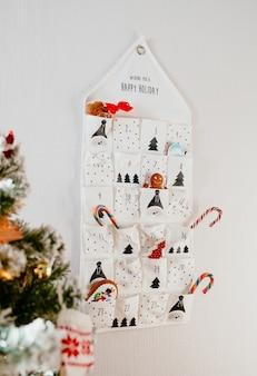 Kerstvakantiekalender met geschenken en snoep hangt aan een muur in een lichte kamer bij de kerstboom
