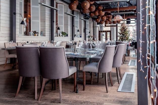 Kerstverlichting, decor, interieur modern restaurant, panoramische ramen, instelling, serveren banket, grijze textiel stoelen, serveertafels, wijnglas, borden, bestek. feestelijk nieuwjaar, winter