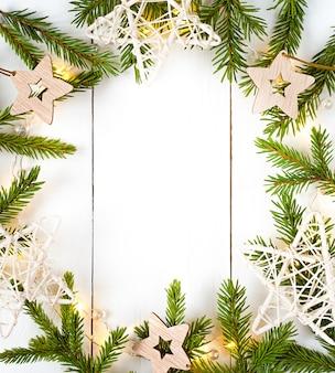 Kerstverlichting garland cirkelvormige rand en dennentakken en witte houten sterren met kopie ruimte.