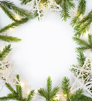 Kerstverlichting garland cirkelvormige rand en dennentakken en witte sterren met kopie ruimte.