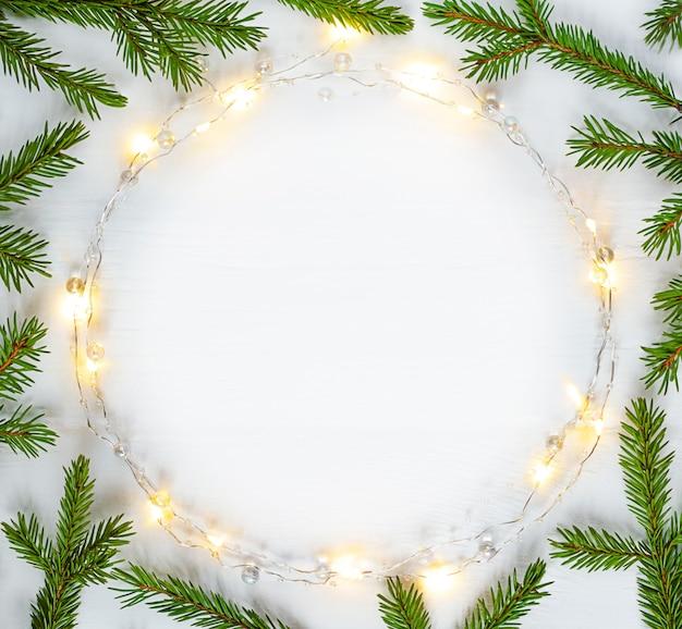 Kerstverlichting garland cirkelvormige rand en dennentakken met kopie ruimte.