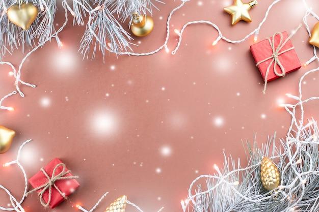 Kerstverlichting, gouden ornamenten, rode geschenkdoos en dennentakken op bruine achtergrond