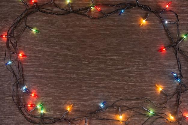Kerstverlichting op donkere houten achtergrond prettige kerstdagen en gelukkig nieuwjaar met kopieerruimte f