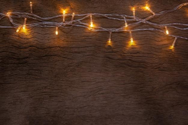 Kerstverlichting op houten plankachtergrond prettige kerstdagen en gelukkig nieuwjaar met kopieerruimte