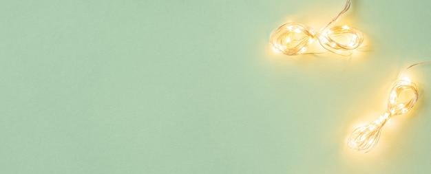 Kerstverlichting op lichtgroene achtergrond plat lag met vakantie garland kopie ruimte