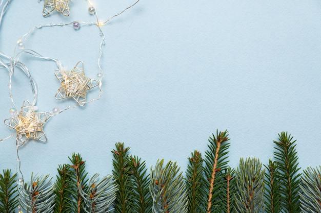Kerstverlichting slingers en fir takken op een blauwe achtergrond
