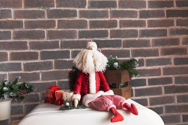 Kerstversiering, een speelgoed kerstman met een witte baard zit tegen een bruine bakstenen muur.